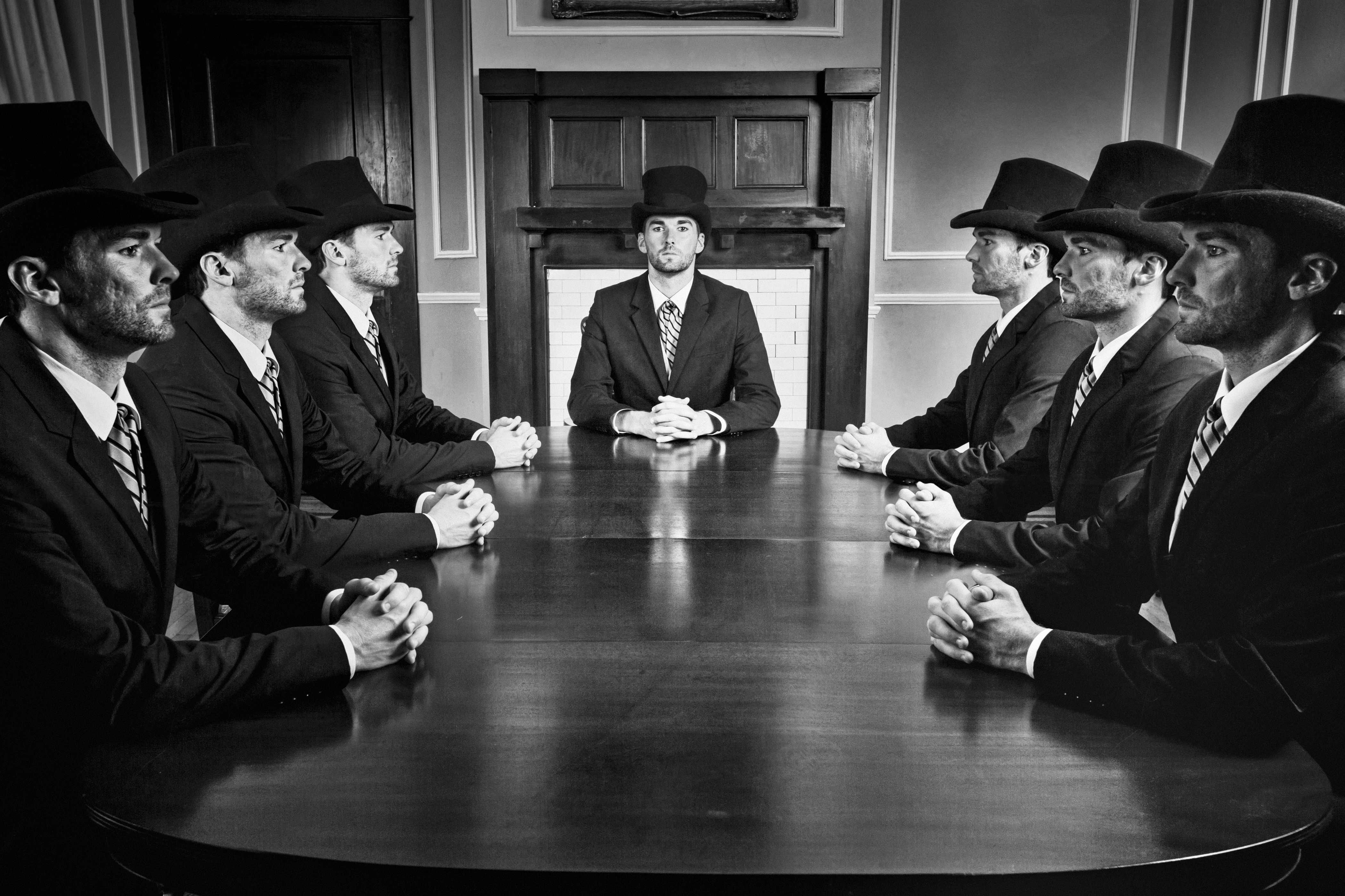Black & White image of a businessman clones on a meeting.